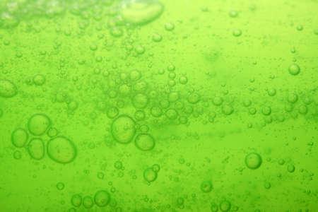 jabon liquido: Verde enmascarado extracto fondo líquido con burbujas de jabón
