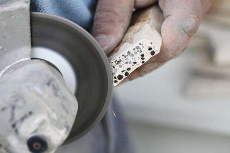 clinker tile: Renovaci�n a los trabajadores a domicilio corta azulejo con amoladora angular herramienta el�ctrica hombre es suelo de baldosas en el sitio de la construcci�n de viviendas Foto de archivo