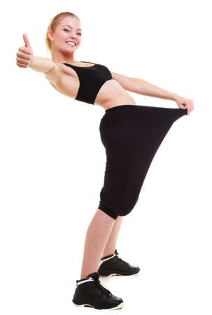 Weight loss, healthy lifestyle. Blonde happy excited woman fitness girl with big pants, showing how much weight she lost, giving thumbs up success hand sign isolated on white background photo