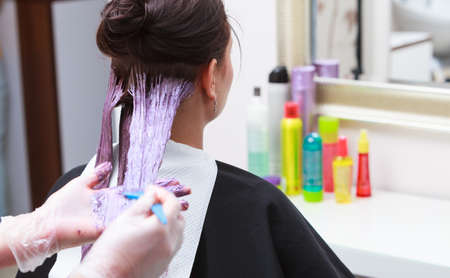 Professional female hairdresser applying color to female customer at design hair salon, woman having her hair dyed, Hair dye colouring in process photo