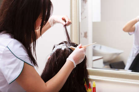 Brunette woman in hairdressing beauty salon. Girl dying hair by hairstylist. hairdresser colouring client hair. photo