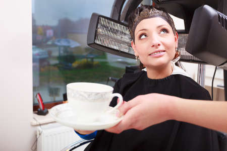Brunette woman in hairdressing beauty salon. Girl dying colouring hair by hairstylist. Hairdresser offering cup of hot beverage coffee tea. Modern professional equipment. photo