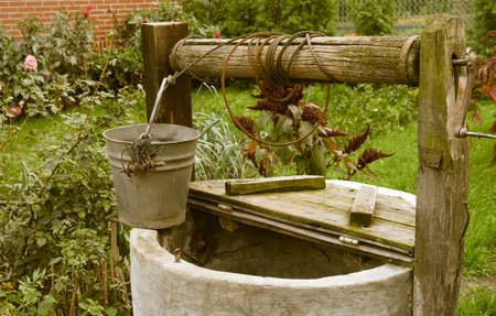 old rotten water well in summer garden, rural scenery outdoor photo