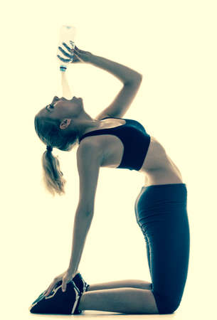 Full length beautiful sporty woman doing stretching exercise drinking water camel pose in silhouette studio shot photo
