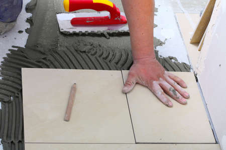 Home improvement, renovation - construction worker tiler is tiling, ceramic tile floor adhesive, trowel with mortar Stock Photo - 23959393