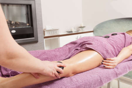 Beauty treatment concept. Woman relaxing getting spa hot stone therapy legs massage procedure in salon. Body care healthy lifestyle. photo