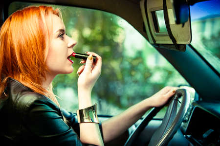 Concept of danger driving. Young woman driver red haired teenage girl painting her lips doing make up while driving the car. photo