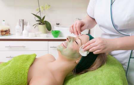 cosmetician: Beauty treatment concept. Woman relaxing in spa salon. Cosmetician removing clay facial mask from female face. Body care healthy lifestyle.