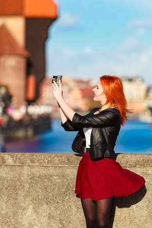 Female photographer taking pictures. Traveler woman red haired fashion girl with camera outdoors in european city, old town Gdansk river Motlawa in the background, Poland Europe photo
