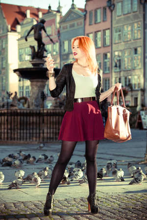 neptun: Full length of fashionable red haired tourist girl young woman taking photo picture of herself with camera in old town Gdansk Danzig, Poland. Fountain Neptun in background. Outdoor. Travel, tourism and landmarks.