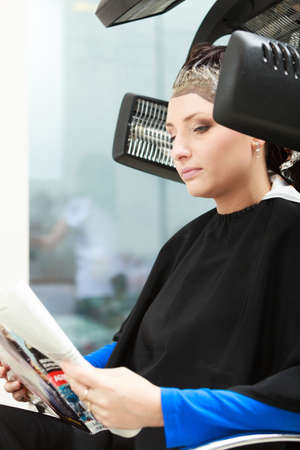 Young woman female client reading magazine relaxing in hairdressing beauty salon  Girl dying colouring hair by hairdresser hairstylist  Modern equipment   photo
