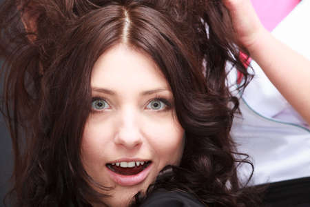 Portrait of surprised schoked beautiful brunette woman with open mouth wide eyed by hairdressing salon. Hairdresser hairstylist combing her client. Close-up. Interior. photo