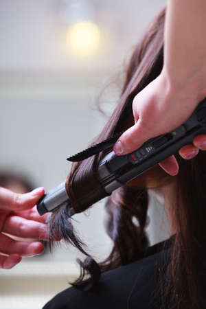 Young woman girl in hairdressing beauty salon. Close-up of brunette female hair and straightening irons in hand of haidresser hairstylist. photo