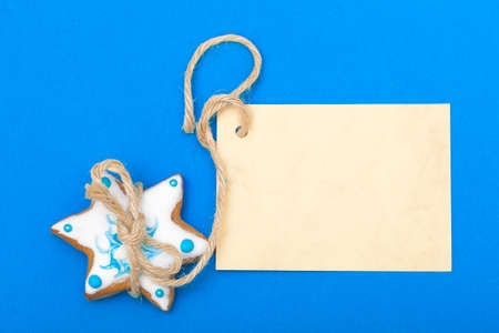 Homemade gingerbread cake star with icing and blue decoration and blank paper card copy-space on blue as christmas background. Holiday handmade concept. photo