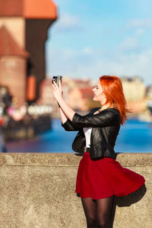 Fashionable red haired tourist girl young woman taking photo picture with camera in old town Gdansk Danzig, Poland. Outdoor. Travel, tourism and landmarks. photo