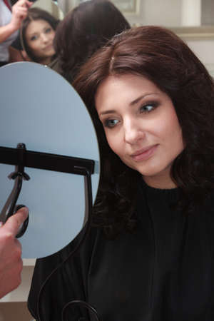 impressed: Portrait of young brunette woman looking at mirror by hairstylist. Girl admiring impressed by new hairstyle by hairdresser. In hairdressing salon. Beauty and relax.