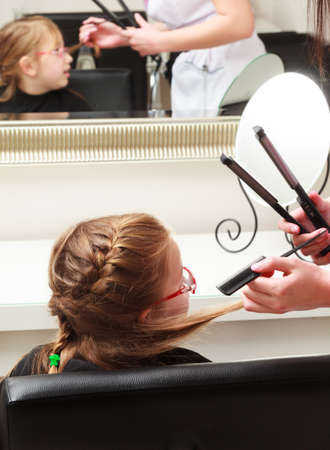 In hairdressing salon. Little girl child sitting on the chair by hairdresser. Hairstylist combing kid with comb interior. photo