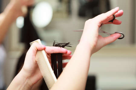 Close-up of hairdresser hands. Hairstylist with comb and scissors cutting hair of female client. Woman in hairdressing beauty salon. photo