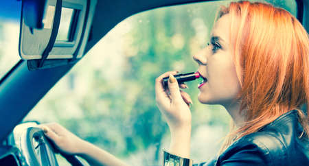 Concept of danger driving  Young woman driver red haired teenage girl painting her lips doing make up while driving the car  photo