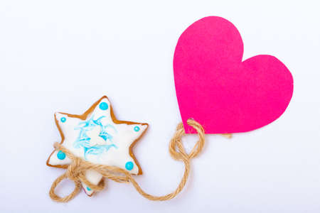 Homemade gingerbread cake star with icing and blue decoration and pink heart love symbol on white as christmas background. Holiday handmade concept. photo
