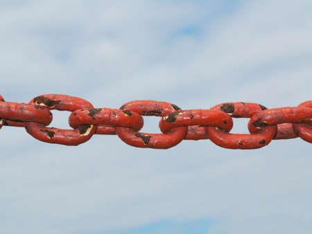 Old rusty metal steel red chain links segment.  Sky cloudy background. photo