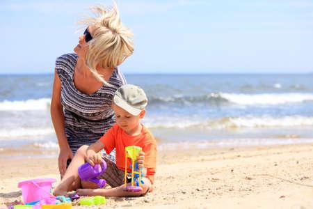 affectionate action: Feliz hijo menor de la familia y de la madre que juega los juguetes en la playa de mar de fondo