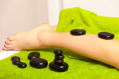 Beauty treatment concept  Woman relaxing getting spa hot stone therapy legs massage procedure in salon  Body care healthy lifestyle   photo