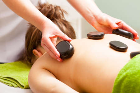 Day-spa. Young woman in green towel relaxing in healthy spa\ salon. Girl having hot stone massage. Indoor.