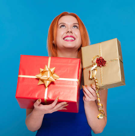 red haired woman: Young happy red haired woman with a gift box present. People celebrating holidays concept. Studio shot blue background