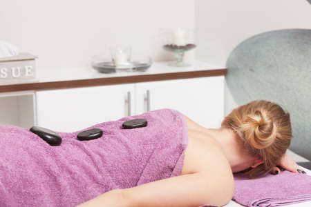 hot stone: Beauty treatment concept. Woman relaxing getting spa hot stone therapy back massage procedure in salon. Body care healthy lifestyle.