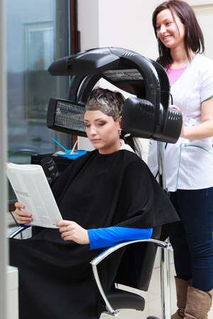 Young woman female client reading magazine relaxing in hairdressing beauty salon. Girl dying colouring hair by hairdresser hairstylist. Modern equipment. photo