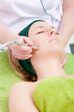 stimulating: Young woman having stimulating facial treatment from therapist. Professional equipment. Healthy beauty spa salon. Stock Photo