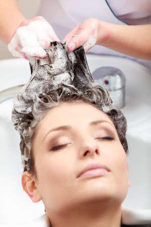 샴푸: 미용사 미용사 세척 고객의 머리. 미용 뷰티 살롱에서 편안한 갈색 머리 소녀 젊은 여자.