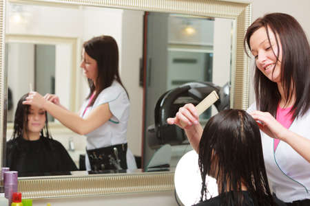 brunette young woman looking at reflection of mirror by hairstylist  hairdresser combing female client  In hairdressing beauty salon   photo
