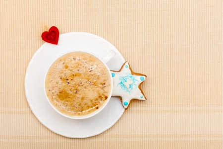 White cup of hot beverage drink coffee cappuccino latte with homemade gingerbread cake star with icing and blue decoration and red heart symbol love  Christmas  Holiday concept   photo