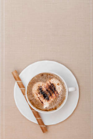 White cup of hot beverage drink coffee cappuccino latte with heart love symbol froth and sweet waffle roll stick with cream on brown background. Studio shot. photo