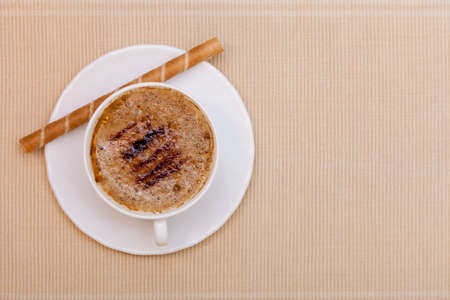 White cup of hot beverage drink coffee cappuccino latte with froth and sweet waffle roll stick with cream on brown background   photo