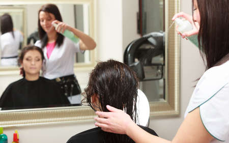 hairspray: Hairstylist with hairspray spraying hair of female client. Woman in hairdressing beauty salon.