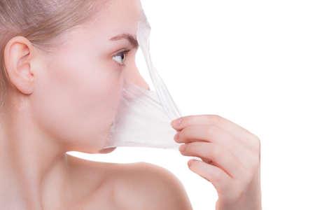 Portrait des blonden Mädchens junge Frau in der Gesichtsmaske ablösen. Peeling. Schönheits-und Körperpflege. Isoliert auf weißem Hintergrund. Studio gedreht. Standard-Bild - 24176927
