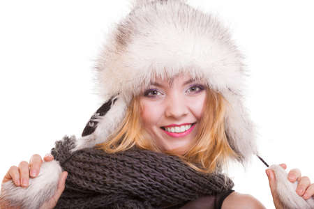 Happy blond girl young woman in warm fur hat. Winter clothes. Fashion and beauty. Studio shot. Isolated on white background. photo