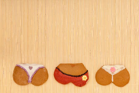 Funny colorfull bikini female panties shape gingerbread cakes cookies sweet dessert with icing and decoration border or frame on beige bamboo mat background photo