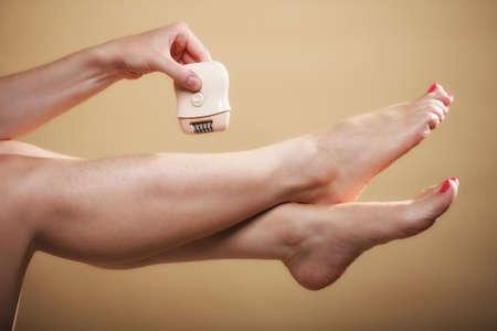 ... Mujer afeitarse las piernas con maquinilla de afeitar depilación cuidado  del cuerpo eléctrico en naranja. Belleza y concepto de cuidado de la piel. c3f50b988d74