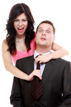 Emancipation idea concept. Humorous funny couple - woman pulling the tie of a man, trying to show her domination, isolated photo