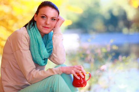 Happiness carefree and nature. Young happy woman relaxing in the autumn park enjoying hot drink coffee or tea, holding red mug with warm beverage. Yellow leaves background photo