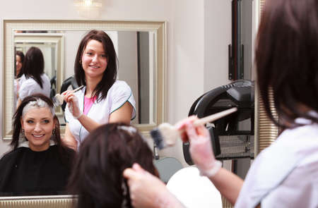 Reflection in mirror. Brunette woman in hairdressing beauty salon. Girl dying hair by hairstylist. hairdresser colouring client hair. photo