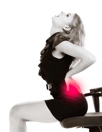 mujeres de espalda: Joven empresaria con dolor de espalda. Mujer rubia con dolor de espalda sentado en la silla. Las largas horas de trabajo. Bussiness. Foto en blanco y negro. Aislado. Estudio de un disparo. Foto de archivo