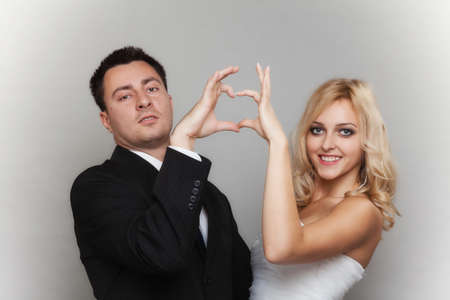 Wedding day. Happy blonde bride and groom showing making heart shape sign with hands gray background photo
