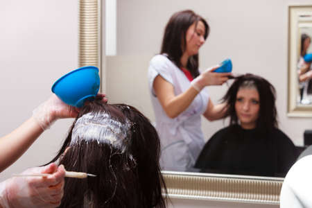 Brunette young woman in hairdressing beauty salon. Girl dying hair by hairstylist. hairdresser colouring client hair. photo