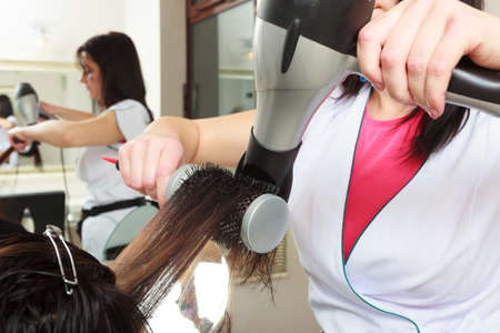 Hairstylist with brush and dryer. hairdresser drying hair of female client. Woman in hairdressing beauty salon. photo