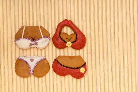 Funny colorfull bikini shape gingerbread cakes cookies sweet dessert with icing and decoration border or space on beige bamboo mat photo